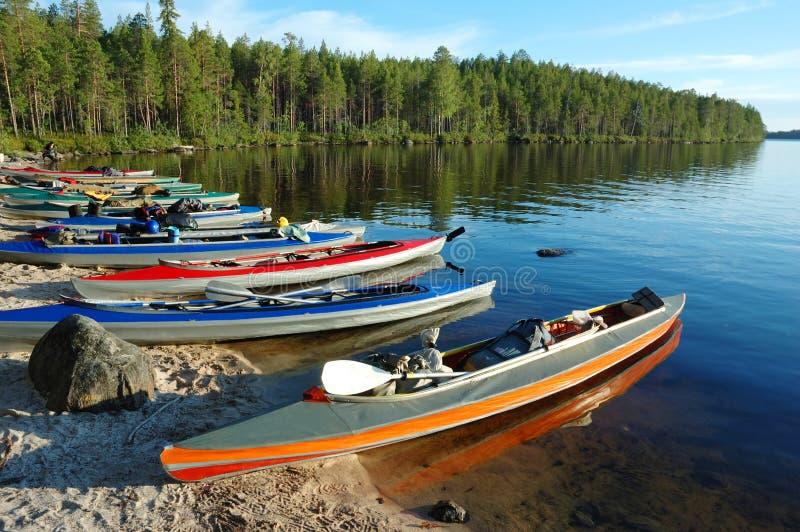 Färgrika kanoter en lake, polara Karelia, Ryssland fotografering för bildbyråer