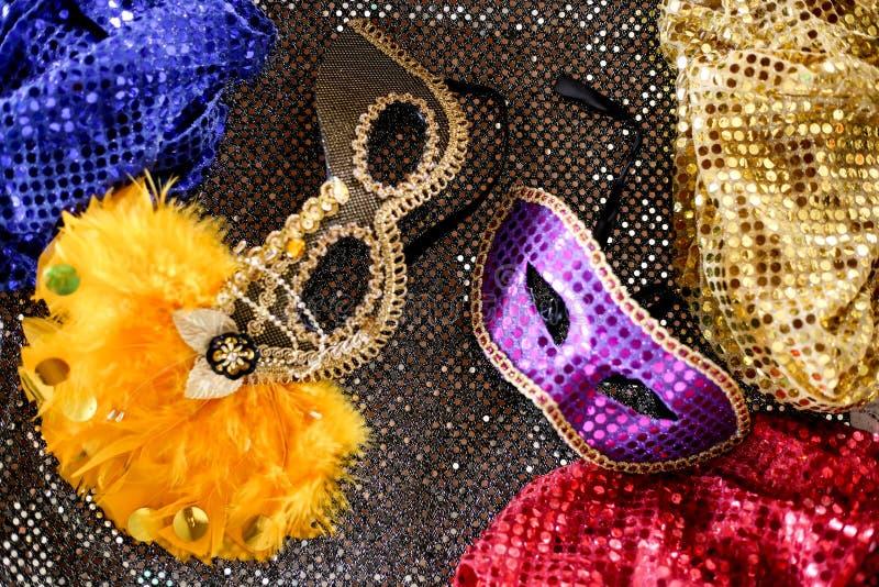 Färgrika karnevalmaskeringar med gula fjädrar med mörkt - grå bakgrund royaltyfria bilder