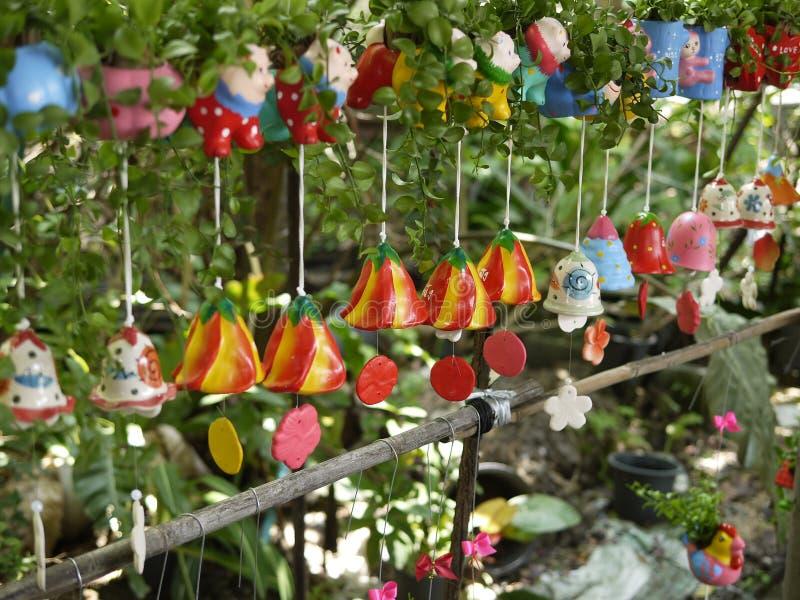 Färgrika keramiska vindchimes med den naturliga miljön i organisk orkidé brukar med liten växter och tecknad filmgarnering arkivbilder