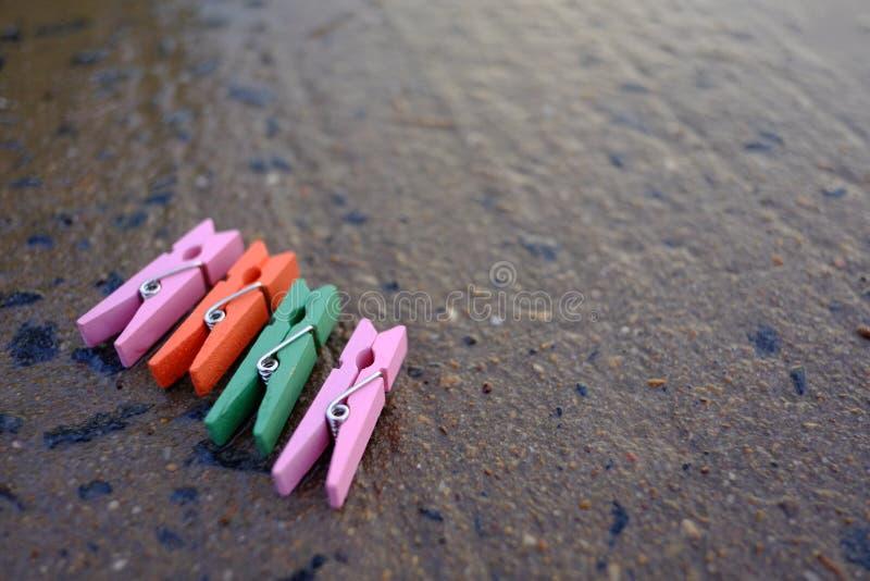 Färgrika klädnypor på våt roadcementbakgrund arkivfoton