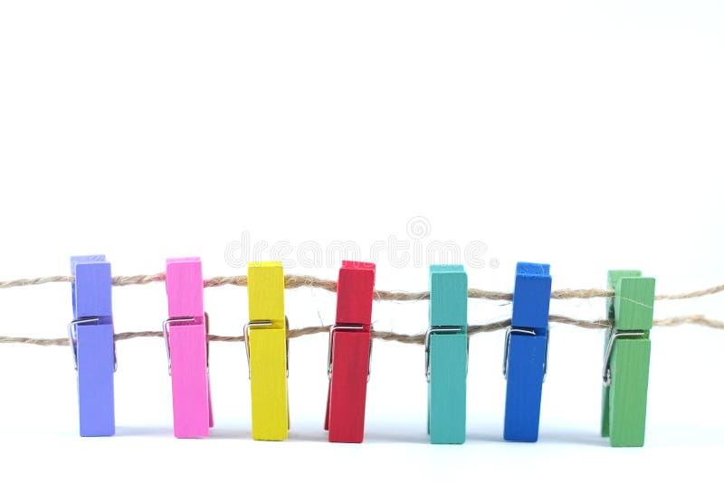 Färgrika klädnypor på vit bakgrund arkivfoton