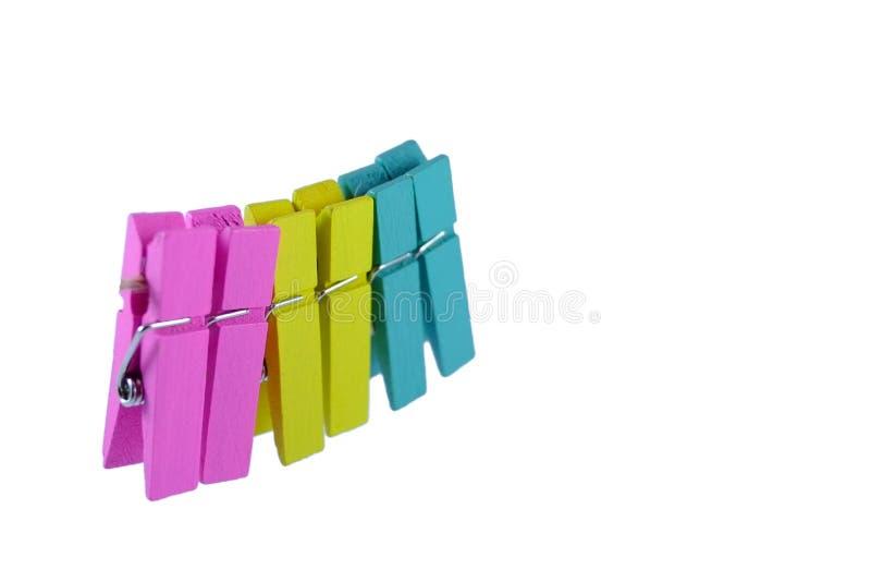 Färgrika klädnypor på vit bakgrund royaltyfri foto