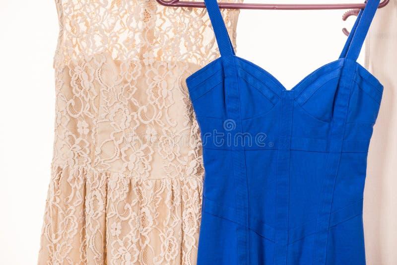 Färgrika klänningar som hänger på klädhängare arkivfoton