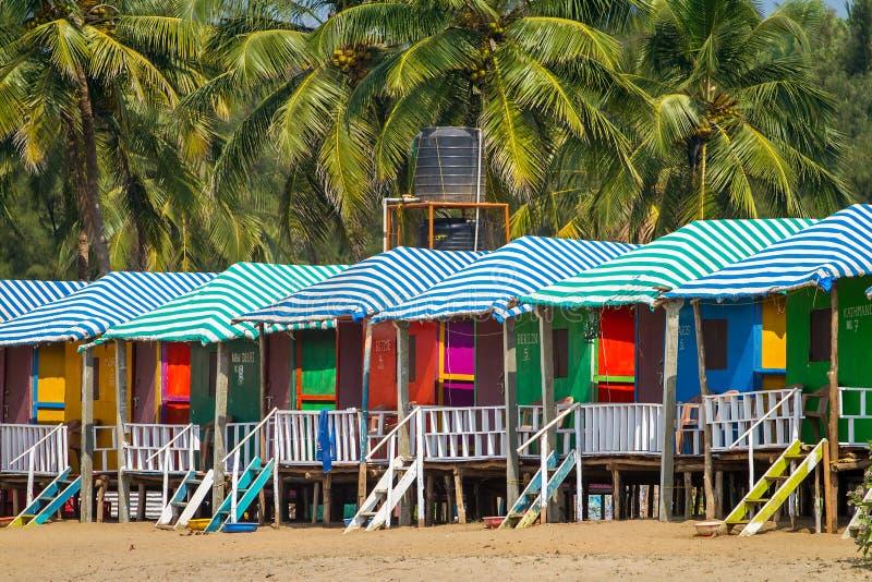 Färgrika kojor på den sandiga stranden i Goa royaltyfri bild