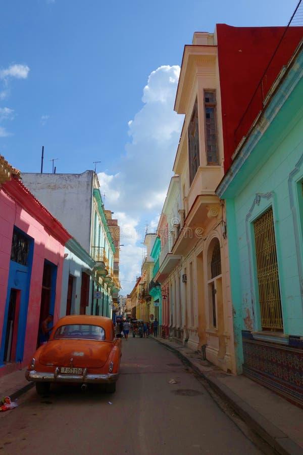 Färgrika koloniala byggnader med den gamla tappningbilen, havannacigarr, Kuba arkivbild
