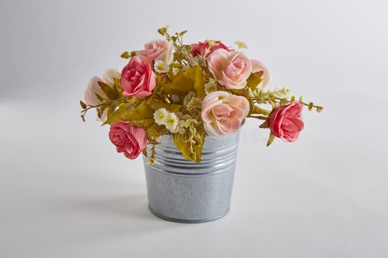 Färgrika konstgjorda rosa blommor i kruka på vit bakgrund arkivfoto