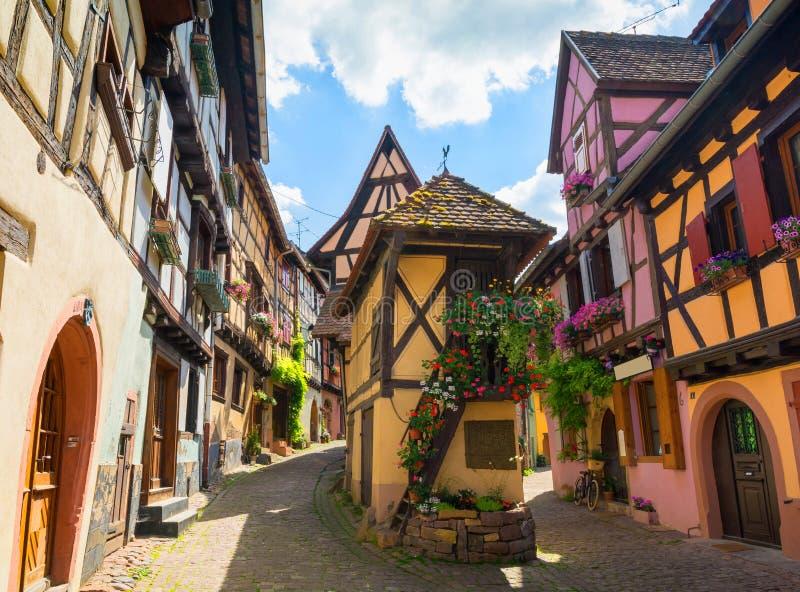 Färgrika korsvirkes- hus på kullerstengränden i den elsassiska staden av Eguisheim, Frankrike arkivfoto