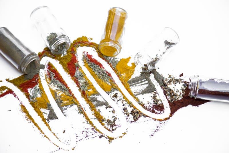 Färgrika kryddor spridda på en vit tabell arkivfoton