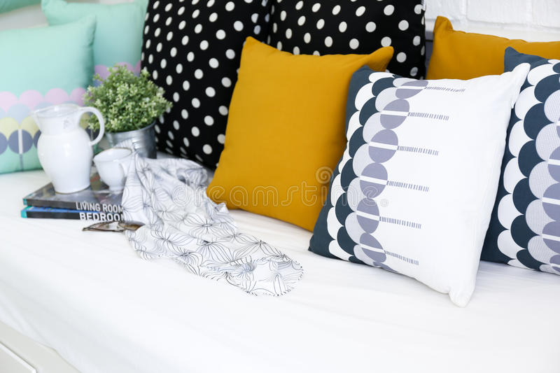 Färgrika kuddar på en soffa med vit tegelstenvägg I arkivbild