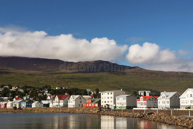 Färgrika kust- hus near grönt berg och vatten, Island, Akureyri royaltyfri fotografi