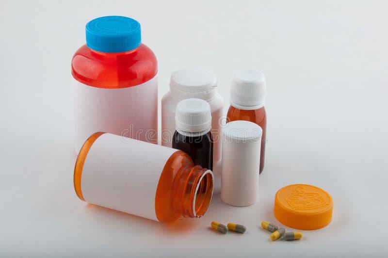Färgrika läkemedelflaskor och preventivpillerar på vit royaltyfri fotografi