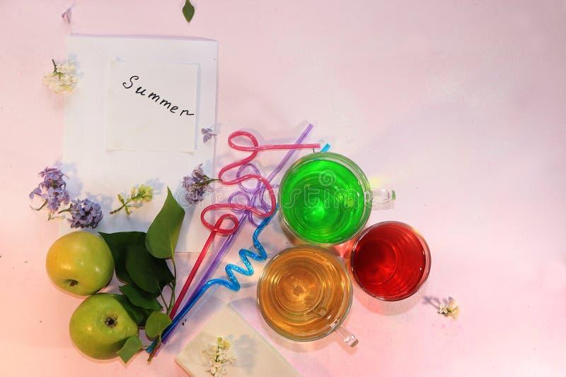 Färgrika lila klungor på en rosa bakgrund, sommardrinkar och frukter, lägger framlänges royaltyfria bilder
