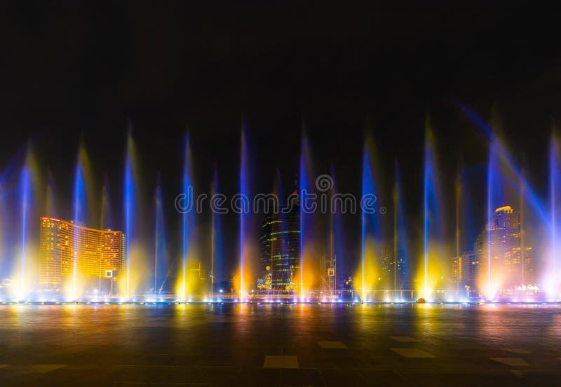 Färgrika ljus med den oskarpa springbrunnen, vattenshow på svart bakgrund i stad på natten arkivfoto