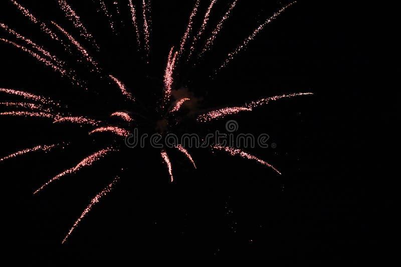 Färgrika ljusa röda fyrverkerier och rök i bakgrunden för natthimmel royaltyfri fotografi