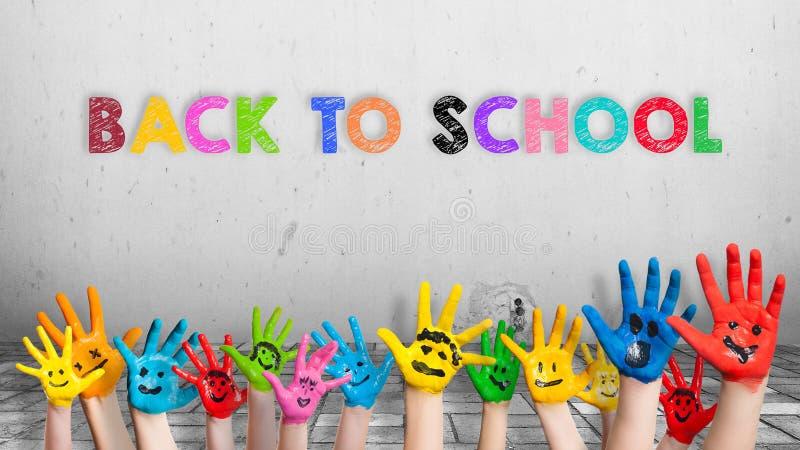 Färgrika målade händer framme av en vägg med en meddelande` tillbaka till skola`, arkivbild