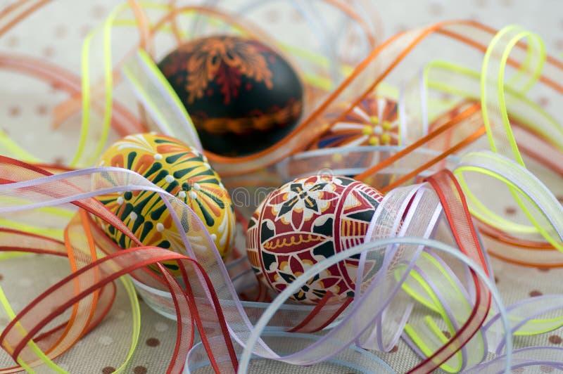 Färgrika målade påskägg på den prickiga bordduken som täckas med ljusa färgrika band, traditionell härlig påskstilleben arkivbild