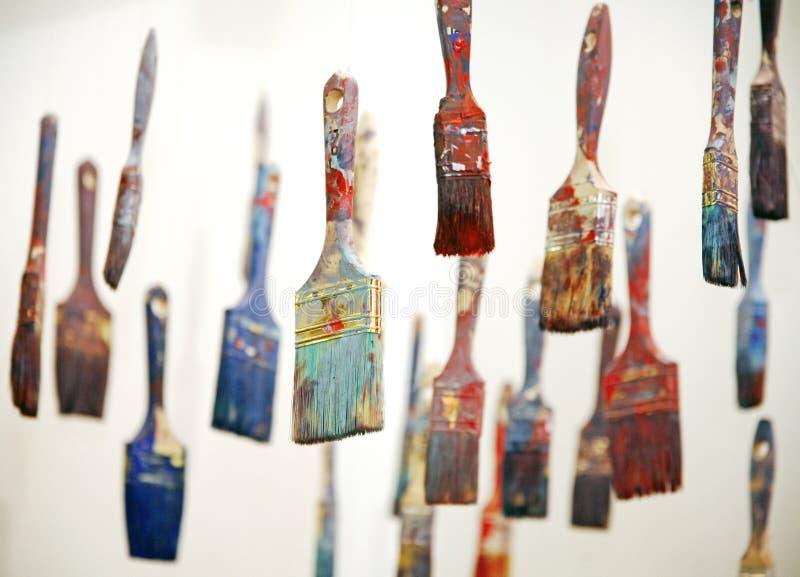 Färgrika målarfärgborstar som hänger som konstnärliga objekt royaltyfri fotografi