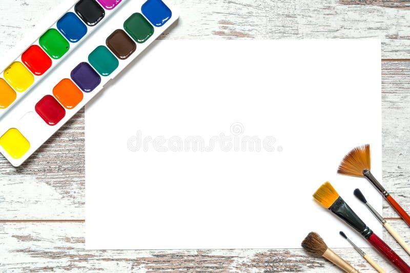 Färgrika målarfärger med borstar och ett isolerat ark av vitbok, gouache, vattenfärg på en träbakgrund för gammal tappning arkivfoton