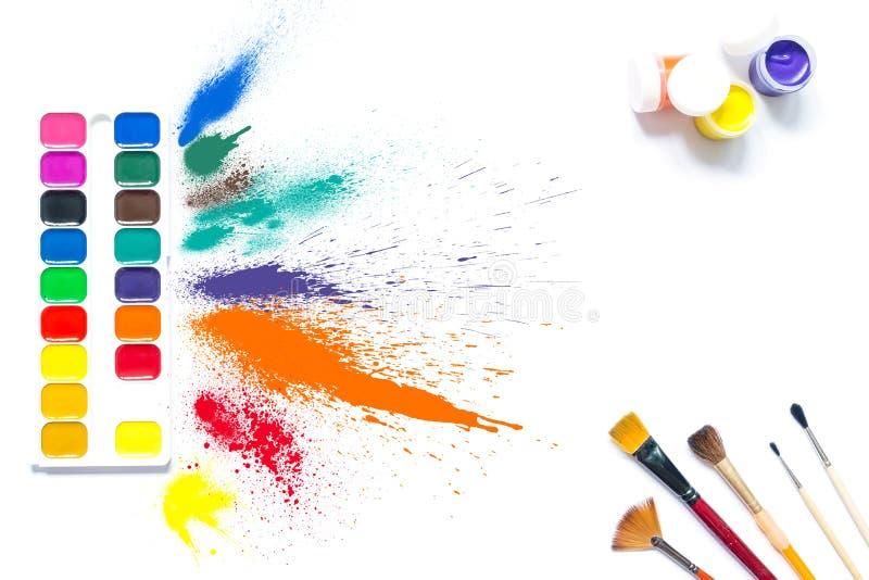 Färgrika målarfärger och borstar med mång--färgad sprejfärgstänkmålarfärg, gouache, isolerad vattenfärg arkivbild