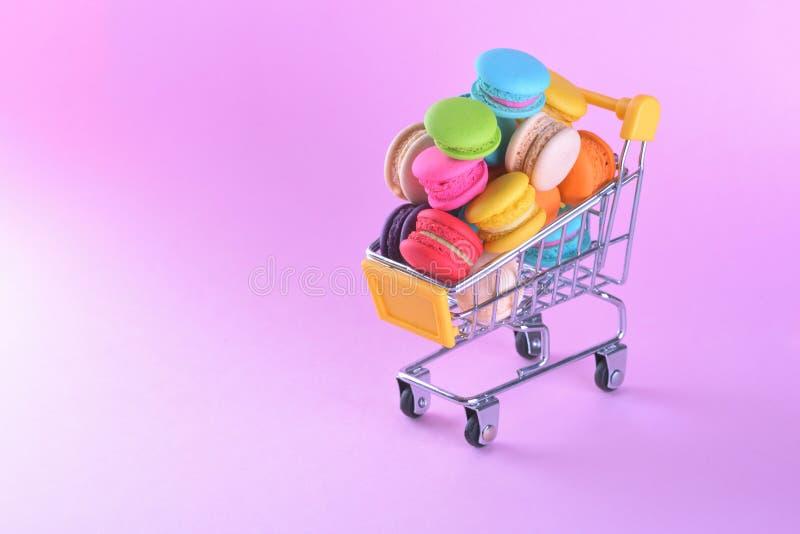 Färgrika macarons eller makron i den söta efterrätten för shoppingvagnen är arkivfoton