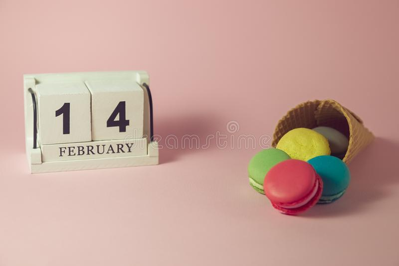 Färgrika macarons i glasskotte med träkalendern på den rosa bakgrunden arkivfoto