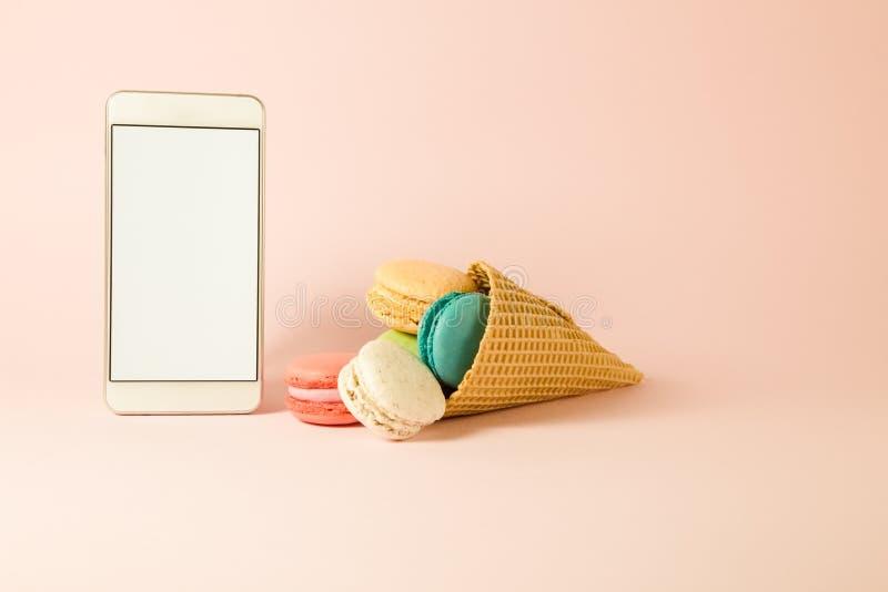 Färgrika macarons i glasskotte och smartphone med den tomma skärmen royaltyfri bild