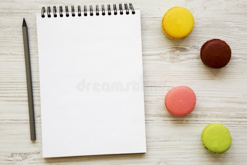 Färgrika macarons och tom anteckningsbok på en vit träbakgrund, sikt från över Lekmanna- lägenhet, över huvudet bästa sikt arkivbild