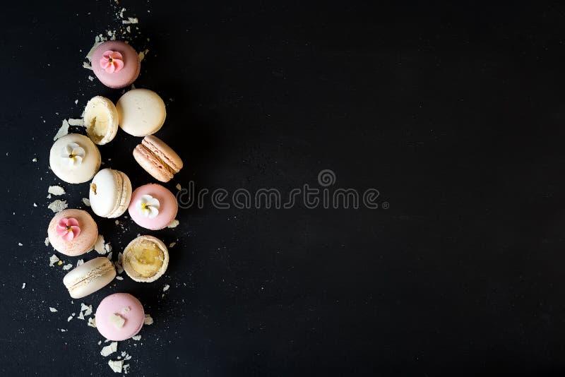 Färgrika macarons på svart stenar bakgrund Bästa sikt med kopieringsutrymme royaltyfri fotografi