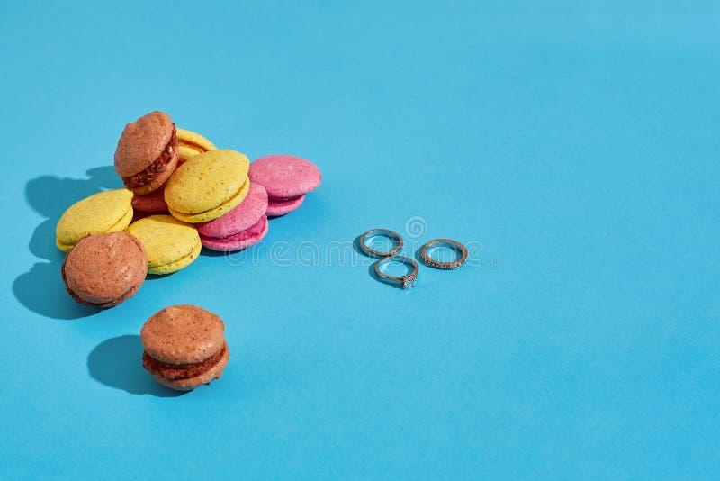 färgrika macaroons ljusa cirklar för bakgrund som gifta sig white ro för cirkel för förslag för förbindelse för bukettdiamantkopp royaltyfri foto