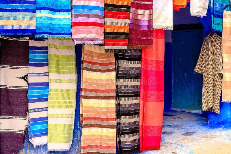 Färgrika marockanska tyger och handgjorda souvenir på gatan i den blåa staden Chefchaouen, Marocko, Afrika royaltyfri foto
