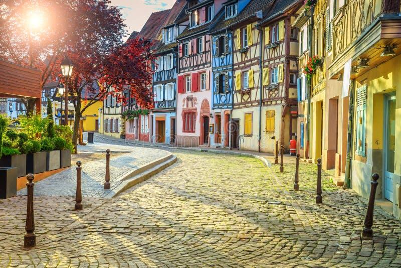 Färgrika medeltida korsvirkes- fasader med den stenlade vägen i Colmar royaltyfria bilder