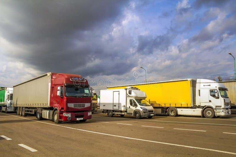 Färgrika moderna stora halv-lastbilar och släp av olikt gör arkivbilder