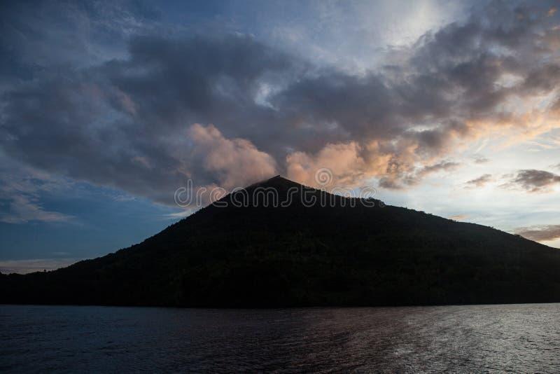 Färgrika moln och vulkan i Banda Islands royaltyfri bild