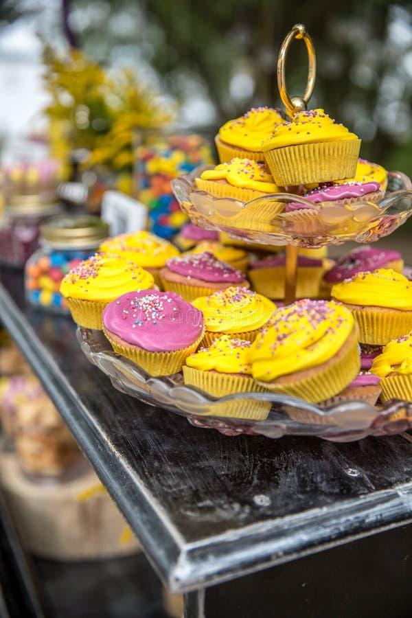Färgrika muffin som glaseras med en variation av glasyr på kakaanstrykningar royaltyfri fotografi