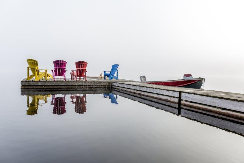 Färgrika Muskoka stolar på en skeppsdocka fotografering för bildbyråer