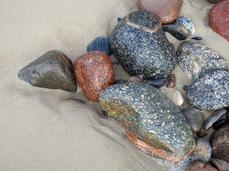 Färgrika naturliga stenar på sand nära havet, Litauen royaltyfri fotografi