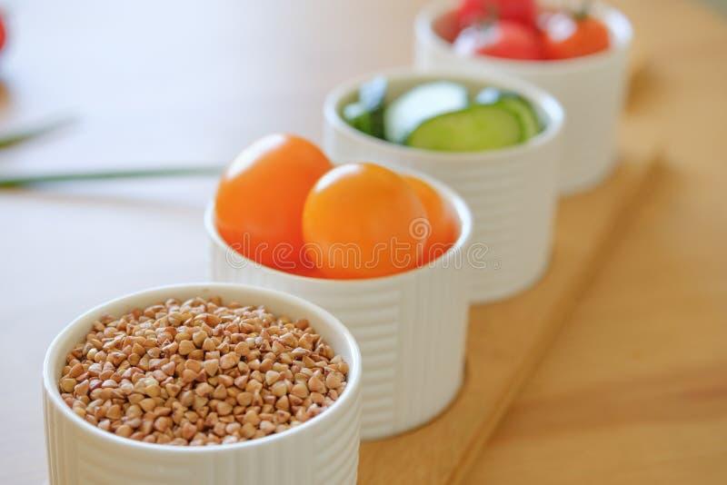 Färgrika nya grönsaker och bovetelögn på en träbakgrund royaltyfri fotografi