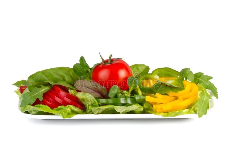 Färgrika nya grönsaker på en plätera, isolerat på vit royaltyfria foton