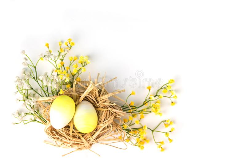 Färgrika påskägg i rede med blommor royaltyfri fotografi