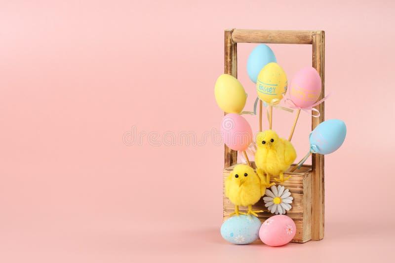 Färgrika påskägg på pinnar och två gulliga hönor i en träblommakorg mot rosa bakgrund lycklig easter h?lsning royaltyfri bild