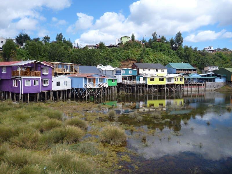 Färgrika palafotoshus på woodelkolonner i chiloeön arkivfoton