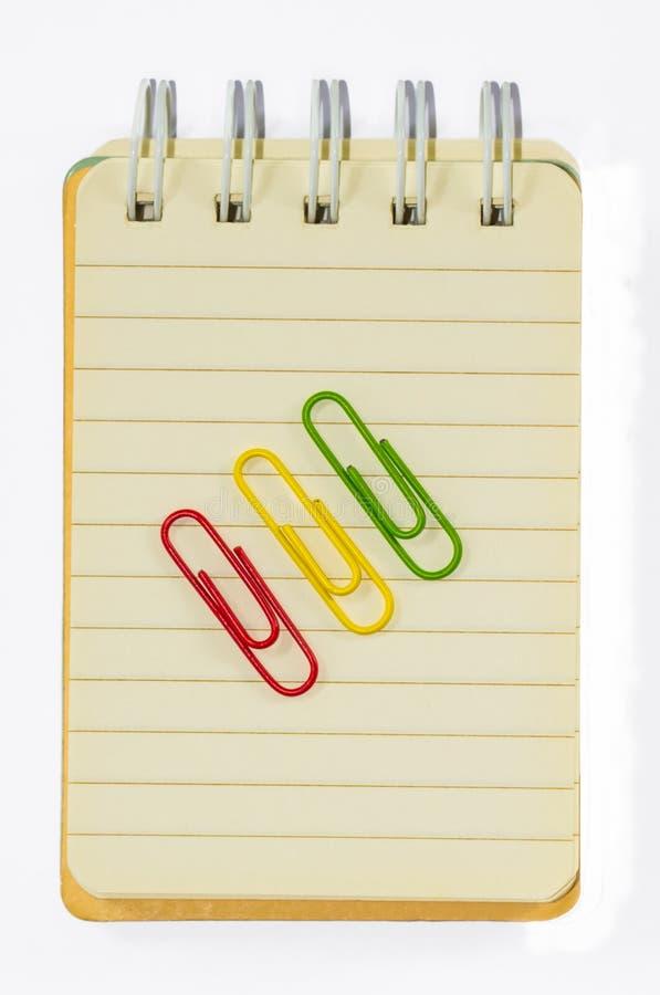Färgrika paperclips och anmärkningsbok på isolerad vit bakgrund arkivfoto