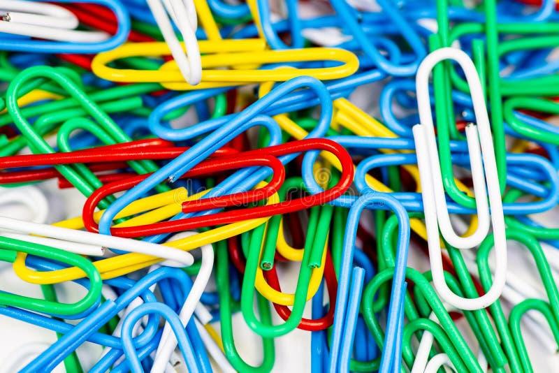 Färgrika paperclips som samlas ihop upp på en vit yttersida arkivbild
