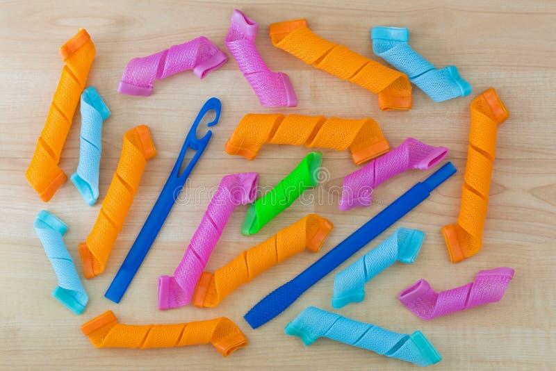 Färgrika papiljotter, långa spirala hårlock, hävstångsverkanrullar med trollstaven till fartfyllt krullningshår royaltyfri fotografi