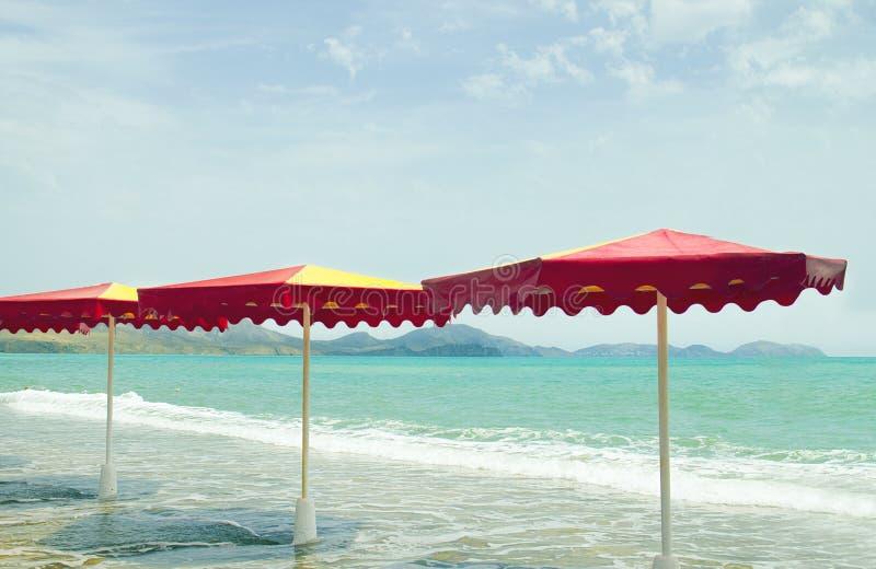 Färgrika paraplyer i stranden, retro stil för tappning royaltyfri foto