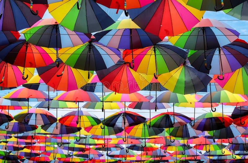 Färgrika paraplyer med färger av regnbågen i den blåa himlen royaltyfri foto