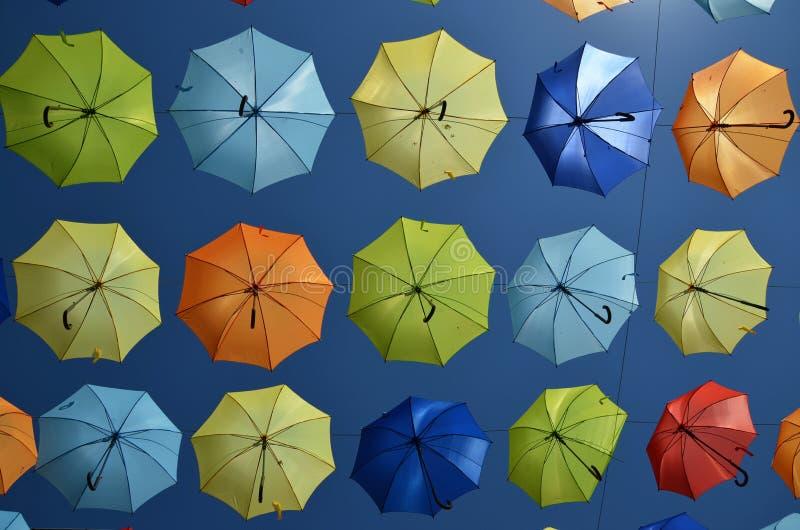 Färgrika paraplyer på luften med klar blå himmel i bakgrunden arkivbilder
