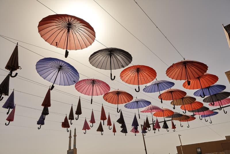 Färgrika paraplyer som hänger från himmelbakgrunden, Yazd, Iran royaltyfri bild