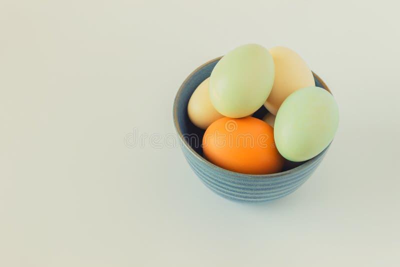Färgrika pastellfärgade ägg i en blå bunke på en vit bakgrund Conce arkivfoton