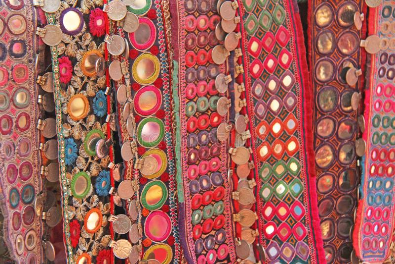 Färgrika person som tillhör en etnisk minoritetbälten med speglar på marknaden i GOA, Indien Tibetana souvenir royaltyfria foton
